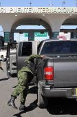 stock photo of smuggling  - An army soldier checking vehicles traveling from Mexico to the U - JPG