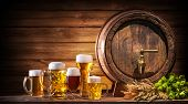 Oktoberfest beer barrel and beer glasses with wheat and hops on wooden table poster