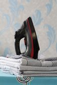 A Black Iron Stands On The Ironing Board. Near A Pile Of Bed Linen. Picture In Blue Tones. Ironing T poster