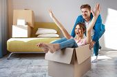Young Family Couple Bought Or Rented Their First Small Apartment. Cheerful Happy People Having Fun.  poster