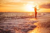 Carefree Woman Dancing In The Sunset On The Beach. Vacation Vitality Healthy Living Concept poster