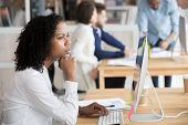 Serious Black Female Employee Thinking Sitting In Front Of Computer poster