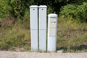 Three Narrow Tall Plastic Electrical Boxes Mounted On Edge Of Asphalt Backyard At Abandoned Industri poster