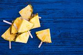 Pineapple  Slice Popsicles On Blue Rustic Wood Background. Summertime Concept. Flat Lay. poster