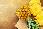 Pineapple On Wood Texture Background. Whole And Sliced Tropical Pineapple On Wooden Cutting Board  W poster