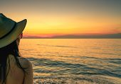 Back View Of Sexy Woman Watching Sunset At The Beach. Woman Wear Sunglasses And Straw Hat Relaxing A poster