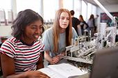 Two Female College Students Building Machine In Science Robotics Or Engineering Class poster