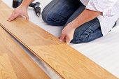 stock photo of wood pieces  - Installing laminate flooring fitting the next piece  - JPG