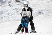 stock photo of snow-slide  - Father supports his child when they slide on alpine skis - JPG