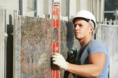 picture of labourer  - Plasterer builder worker with level examining granite stone marble facade works - JPG
