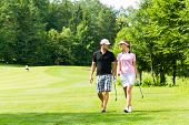 stock photo of golf  - Young sportive couple playing golf on a golf course - JPG