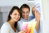 image of 35 to 40 year olds  - Couple choosing paint colour for their new home - JPG