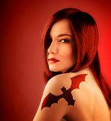 picture of vampire bat  - Photo of beautiful sexy girl with bat tattoo on shoulder isolated on red background - JPG