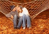 Image of happy couple swinging in hammock, young family having fun in autumn park, best friends rest