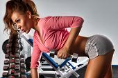 picture of health center  - Woman with dumbbells in sport center - JPG