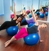 stock photo of stability  - Pilates aerobics women group with stability ball in a row on mirror gym - JPG