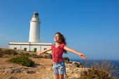 stock photo of mola  - blue day with kid girl open hands to the wind in la Mola lighthouse of Formentera - JPG