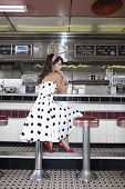 foto of diners  - Full length side view of a young woman sitting at the diner counter - JPG