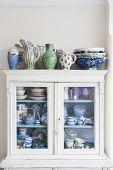 stock photo of crockery  - Crockery displayed in storage cabinet at home - JPG