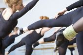 stock photo of ballet barre  - Group of ballet dancers practicing in rehearsal room - JPG