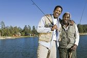 image of fishing rod  - Portrait of happy senior man and adult son holding fishing rods by lake - JPG