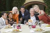 Group of multiethnic friends posing for photograph at the outdoor dining table