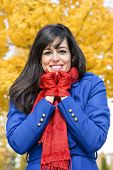 picture of shivering  - Brunette woman wearing blue coat and red scarf and gloves is cold but smiling with autumn tree on background - JPG