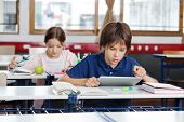 stock photo of concentration  - Little school boy using digital tablet with girl studying in background at classroom - JPG