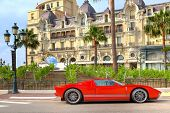 MONTE CARLO, MONACO - JULY 13: Red sports car and Hotel de Paris - luxury hotel opened in 1863, cont