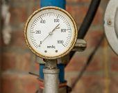 pic of air pressure gauge  - Rusty Pressure Gauge connected to pipes with brick wall behind - JPG