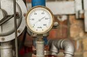 foto of air pressure gauge  - Rusty Pressure Gauge connected to pipes with brick wall behind - JPG