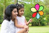 Happy Indian family outdoor activity. Candid portrait of parent and child playing windmill at garden
