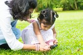 stock photo of peeking  - Cute Indian girl peeking through magnifying glass with parent on green lawn - JPG