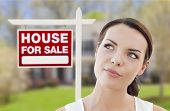 image of yard sale  - Thoughtful Pretty Mixed Race Woman In Front of Home and House For Sale Real Estate Sign Looking Up and to the Side - JPG