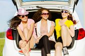 foto of lady boots  - Three young pretty lady sitting in car boot - JPG