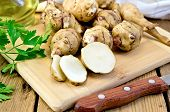pic of jerusalem artichokes  - One cut and a few whole tubers of Jerusalem artichoke with parsley knife and vegetable oil decanter on a wooden board