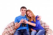 image of coca-cola  - Young couple sitting on a sofa and drinking Coca Cola - JPG