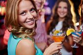 foto of cocktail  - Portrait of cheerful girl holding cocktail in martini glass and looking at camera on background of her friends at party - JPG