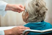 picture of hearing  - Doctor inserting hearing aid in senior - JPG