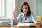stock photo of concentration  - Teenage girl studying reading book at home concentrating looking down - JPG