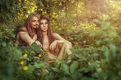 stock photo of wench  - Wild man and woman sitting in the woods in the bushes - JPG