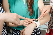 picture of watch  - Asian woman using wearable watch and showing to her friends - JPG