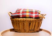 picture of loincloth  - Colorful loincloth fabric on rattan basket on wooden circle stand - JPG