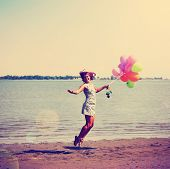 picture of single woman  - a pretty woman enjoying summer outside with a bunch of balloons toned with a retro vintage instagram filter  - JPG