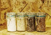 stock photo of rice  - four jars of rice varieties in glass: brown rice mixed wild rice, jasmine rice, rice burry on wood shelf