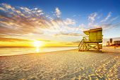 stock photo of sunrise  - Miami South Beach sunrise with lifeguard tower and coastline with colorful cloud and blue sky - JPG
