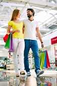 picture of amor  - Amorous couple with paperbags buying presents in the mall - JPG