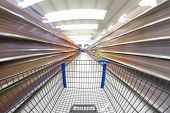 stock photo of grocery cart  - Empty shopping cart moves quickly through a grocery  department store - JPG