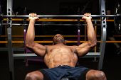 stock photo of bench  - Weight lifter at the bench press lifting a barbell on an incline bench - JPG