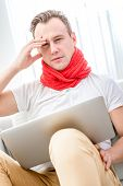 pic of rhinitis  - Ill man suffering from rhinitis sitting on the couch with red scarf at home - JPG